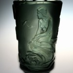 <strong>Hloušek Rudolf</strong> - <p>The vase, smoke coloured glass with etched motive of a&nbsp;ship and girl at sea-shore. Marked Original R. Hloušek Žel. Brod 1935, height 24 cm.</p>